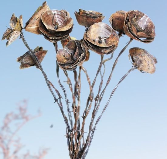 Rusty barbed wires and metal bring exquisite flower